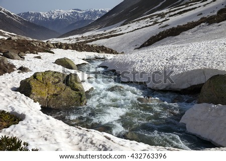 River with snow bridges in spring mountains at sun day. Turkey, Kachkar Mountains, highest part of Pontic Mountains. - stock photo