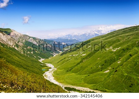 Riverbed between green hills. Snow-capped Caucasus Mountains on background. Summer landscape in Georgia - stock photo