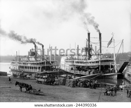 Riverboats on the Mississippi River receiving cargo and supplies at the Vicksburg landing. African Americans provide the hard labor of loading the boats. Ca. 1905. - stock photo