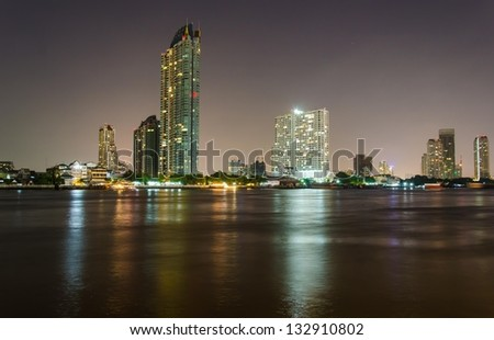 Riverside buildings at night in Bangkok, Thailand.