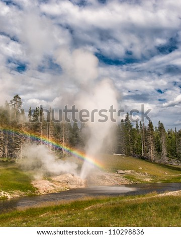 Riverside Geyser creates a rainbow as it erupts during the late afternoon in Yellowstone National Park, Wyoming - stock photo