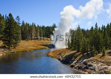 Riverside Geyser errupts on a summer afternoon in the Upper Geyser Basin.  Yellowstone National Park, Wyoming - stock photo
