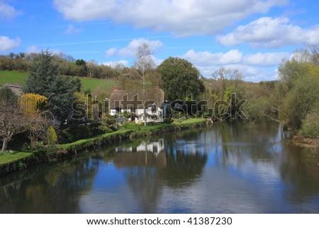 Riverside thatched cottage in Devon UK - stock photo