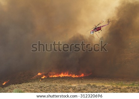 Riverside, WA, USA August 18, 2015: Okanogan Complex Fire. A helicopter negotiates its way thru heavy smoke to help fight Washington state's largest and most destructive fire in history - stock photo