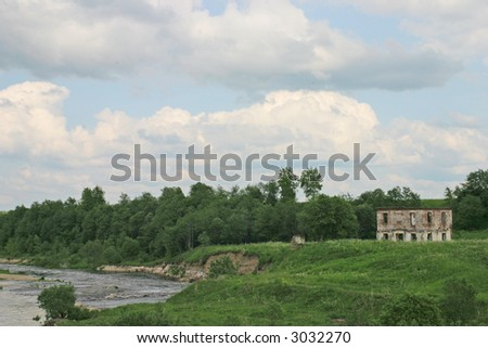 Riverside with ruins of old house under cloudy sky - stock photo