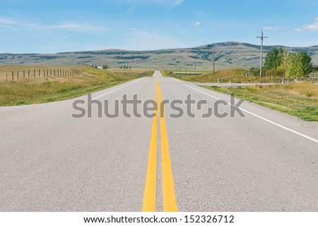 Road across the plains near Fort MacLeod, Alberta, Canada
