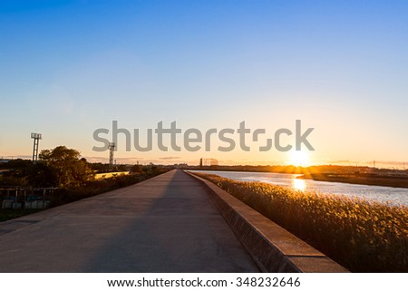 Road along a river at sunset in autumn.
