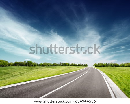 Road along green grassy field. Summer landscape with clouds above trees