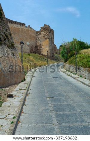 Road among the ruins of the old castle - stock photo