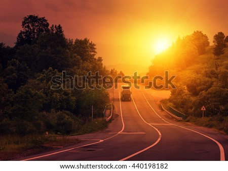 Road and blurred truck on the move. Sunset colors of sky