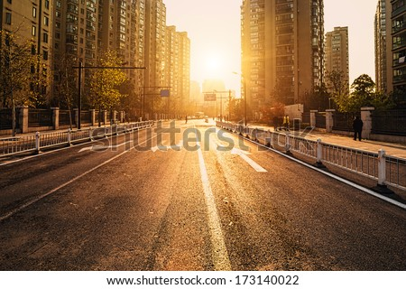 road and buildings at city with sunset - stock photo