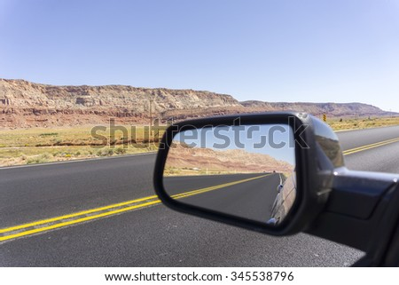 Road and landscape in rear vision mirror through  Arizona. - stock photo