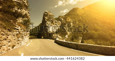 Road and rocks in the mountains in summer - stock photo