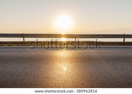 Road and sea in sunset time with burning sun - stock photo