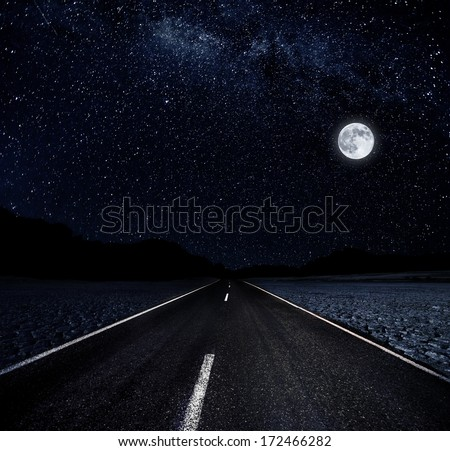 Road and the moon on a starry night in desert - stock photo