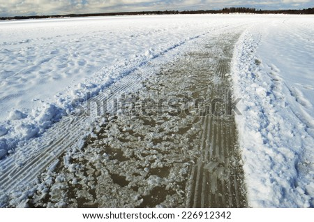 road and tracks on frozen snowcovered lake, horizontal - stock photo