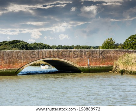 Road arch over Norfolk Broads river with small white rowing boat moored by the bank - stock photo