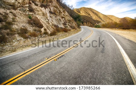 Road bends into the hills of southern California. - stock photo
