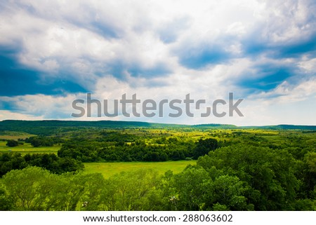 Road between green hills and meadows in the sky clouds storm clouds - stock photo