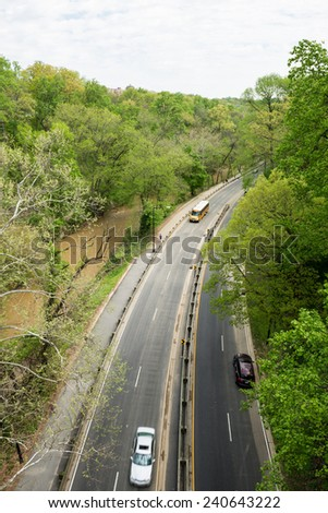 road between tree along the creek with cars and a school bus running through