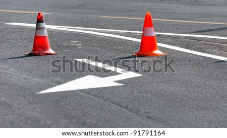 Road block with white arrow showing the alternate way - stock photo