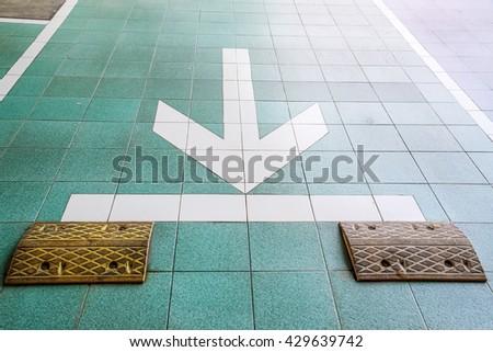Road bump and white arrow - stock photo