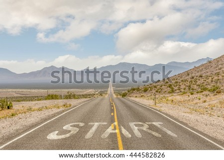 """ROAD Business concept road concept of start up for business with long road, with word """"start"""" on asphalt"""" with blue sky, mountain and cloud background (street, road, highway, tollway, travel, nature)  - stock photo"""