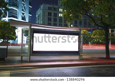 Road car light trails through at modern city advertising light boxes - stock photo