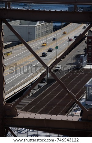 Road, cars and traffic in New York behind metal structure