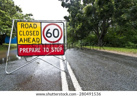 Road closed ahead prepare to stop traffic warning sign on flooded road. Image taken in Queensland, Australia. - stock photo