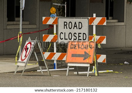 Road closed and detour signs at a downtown urban construction site - stock photo