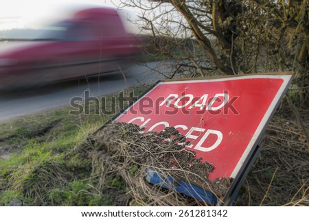 Road closed sign left at a roadside with a vehicle passing at speed - stock photo
