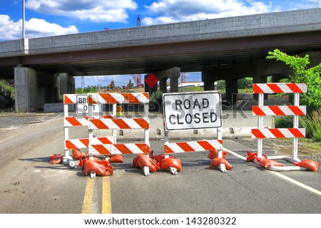 Road closed warning safety sign on traffic barriers on an American road near super highway bridge with improvement construction work site - stock photo