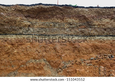 Road collapses.Layer of soil beneath section - stock photo