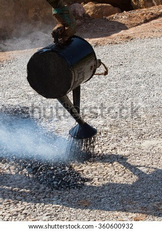 Road construction, old fashioned way of working in the industry with molten asphalt in developing country - stock photo