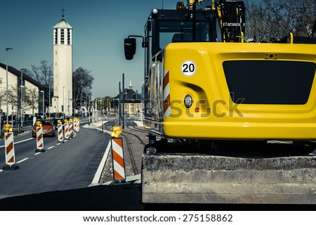 Road construction site in european city with excavator (filtered) - stock photo