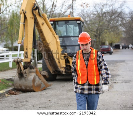 Road construction worker, walks determinately toward the camera. Bulldozer and residential area on the background.