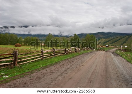 Road, fence and fields. Altay. Russia. - stock photo
