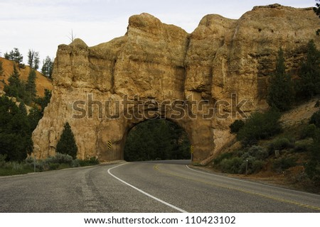 Road  going through a tunnel of rock turning right. - stock photo