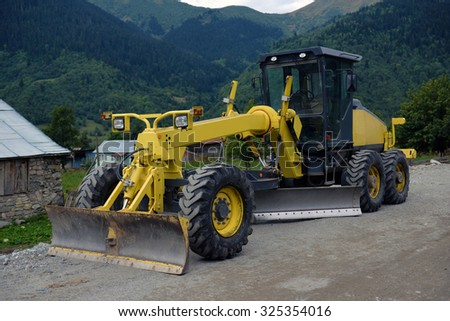 Road grader - heavy earth moving road construction equipment - stock photo