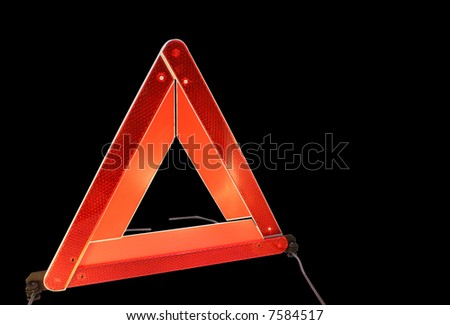 Road hazard warning triangle isolated on a black background