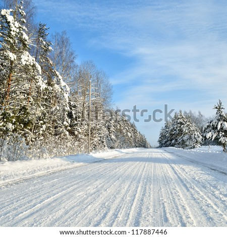 Road in a countryside in sunny winter day. Classic snow covered winter landscape - stock photo