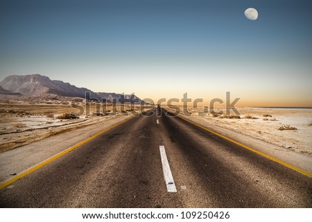 road in desert under the moon - stock photo