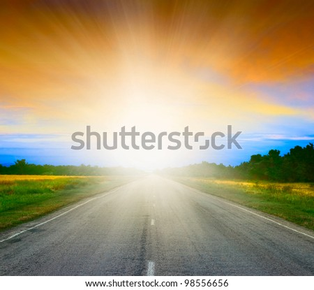 Road in field at early morning. SUnrise. - stock photo