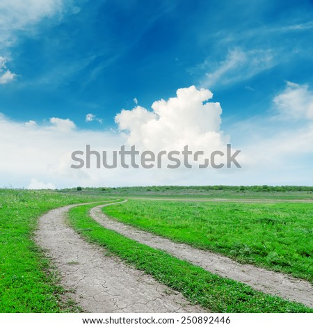 road in green grass under deep blue sky - stock photo