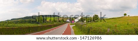 Road in hill landscape with blue cloudy sky. Panoramic shot. Zuid Limburg. The Netherlands. - stock photo