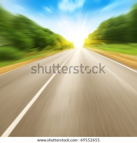 Road in motion blur and blue sky with sun. - stock photo