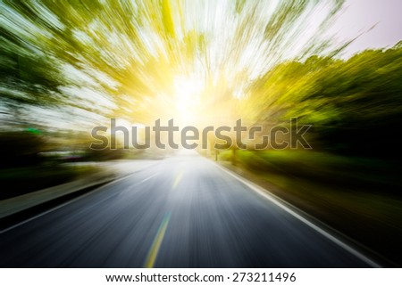 Road in motion blur�¯�¼? through the forest in sunset. - stock photo