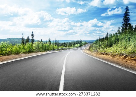 road in mountain forest - stock photo