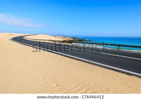 Road in sand dunes landscape of Corralejo National Park, Fuerteventura, Canary Islands, Spain - stock photo